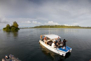 group of men are riding in the powercat by surf banyak