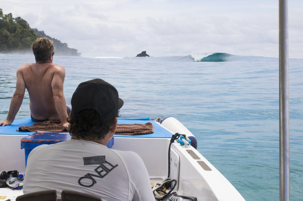 two men in powercat relaxing and watching waves, surf banyak