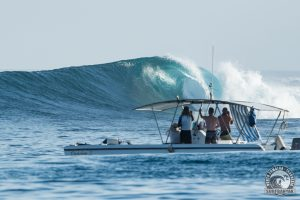 powercat boat with a huge beautiful wave by surf banyak